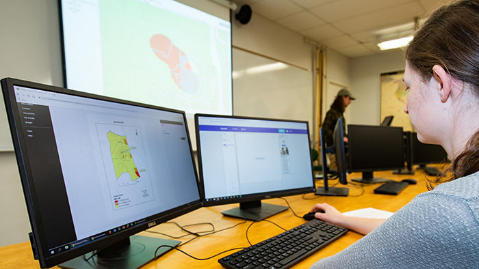Student using dual monitors to complete a GIS project.